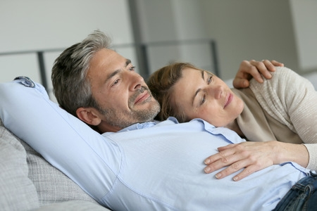 38883598 - mature couple relaxing in sofa, peaceful scene