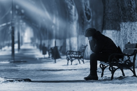 46471589 - sad woman sitting on a bench in winter time.